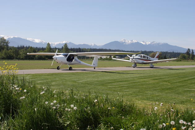 Paul Kuntz' Sinus N54PK and my Warrior N313DC on Paul's taxiway at Sequim Valley airport on 10 May 2013.